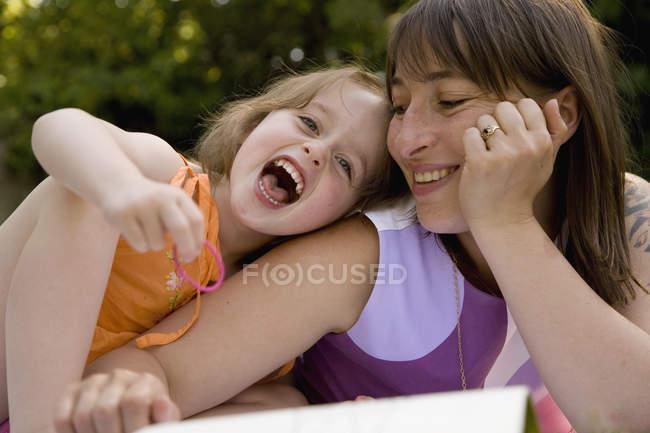 Madre e figlia sdraiati e ridendo insieme nel cortile — Foto stock