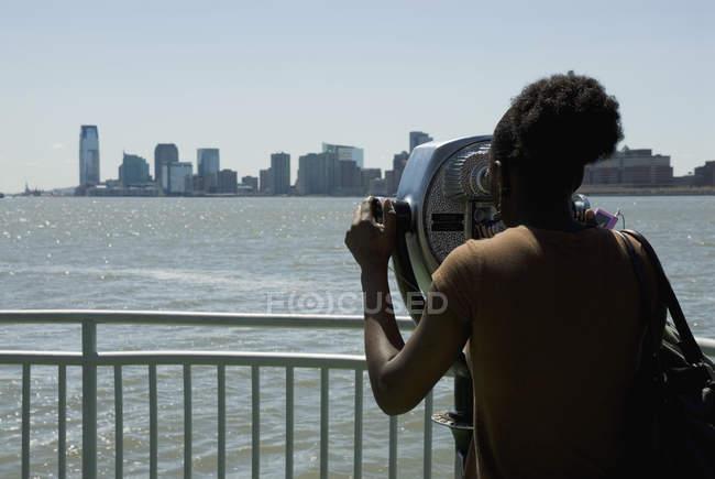 Vista posteriore della donna che osserva al paesaggio urbano attraverso macchina binocolo visite — Foto stock