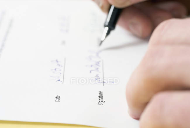 Close-up of Person signing paperwork with pen — Stock Photo