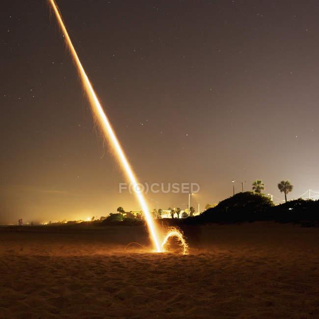 Foto de larga exposición de fuegos artificiales explotando en la playa por la noche - foto de stock