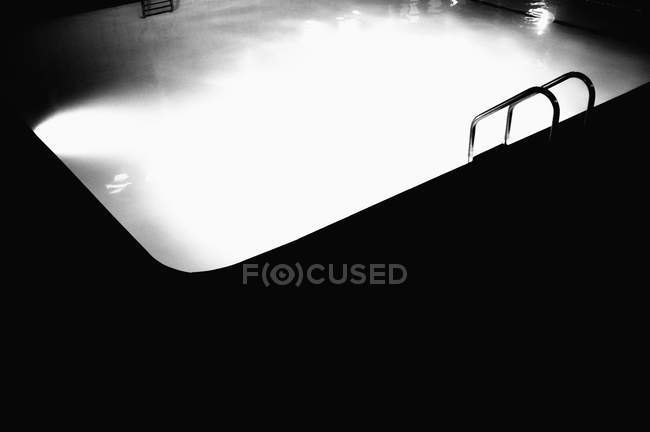 Shadowed poolside contrasting brightly lit water — Stock Photo
