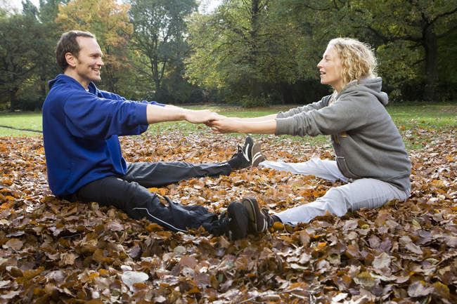 Man and woman sitting and stretching on autumn leaves in park — Stock Photo
