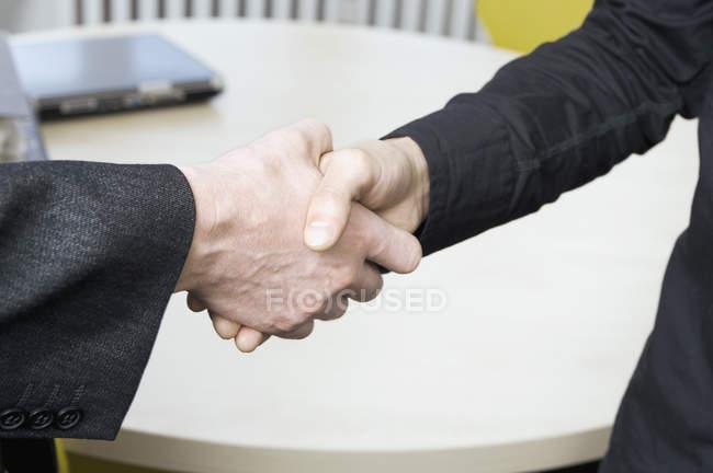 Abgeschnitten Bild zweier Menschen, die Hände schütteln — Stockfoto