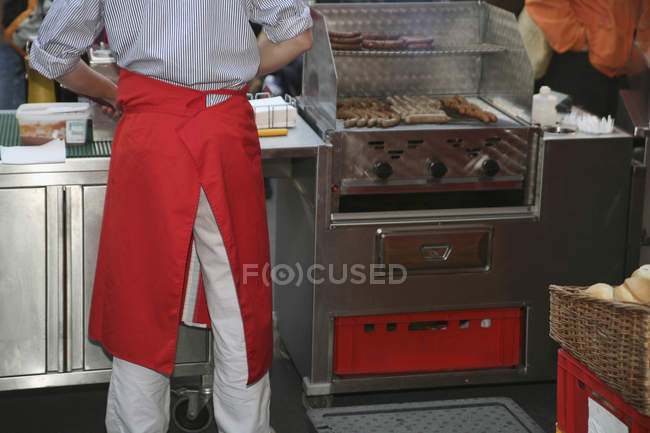 Mid section of market vendor cooking sausages at stall — Stock Photo