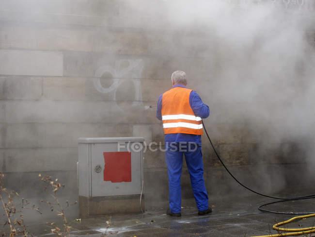 Vista trasera del trabajador quitando graffiti con manguera de presión - foto de stock