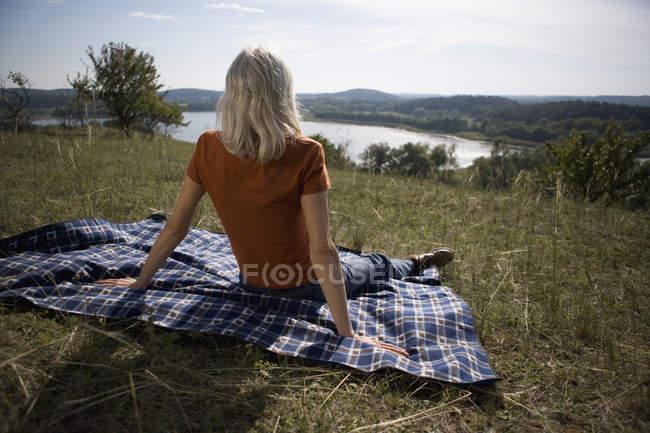 Жінка сидить на пагорбі і, дивлячись на вигляд в природі — стокове фото