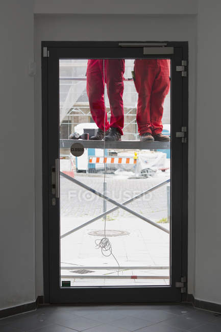 Low section of two construction workers on scaffolding seen through glass — Stock Photo