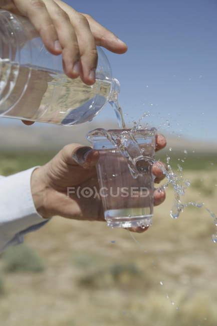 Cultiver les mains verser un verre d'eau dans le désert — Photo de stock