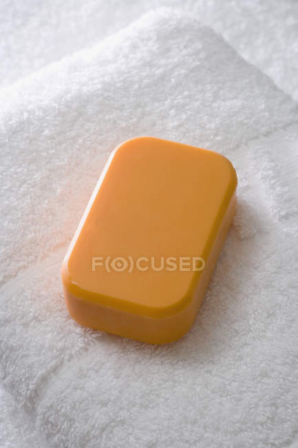 Close up view of bar of soap and towel — Stock Photo