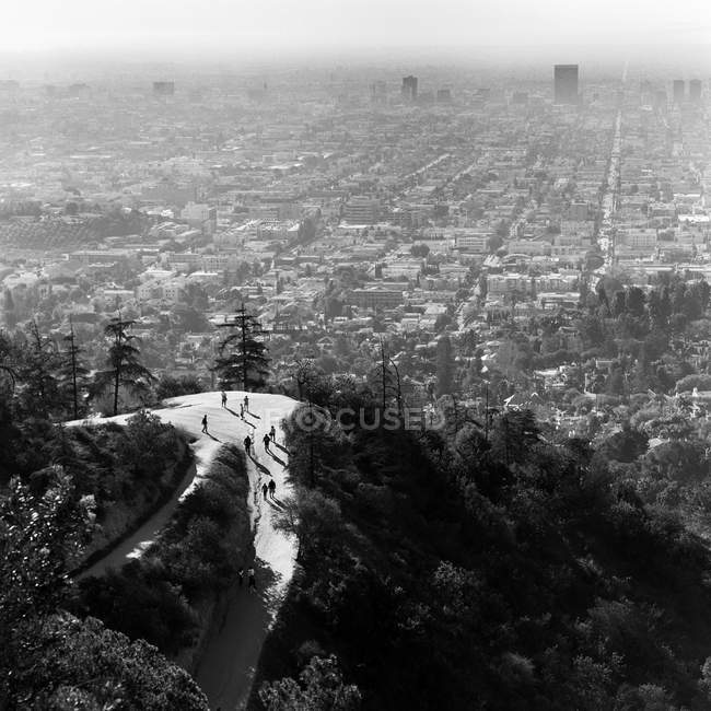Vista aérea de pessoas subindo a colina de floresta contra a paisagem urbana — Fotografia de Stock