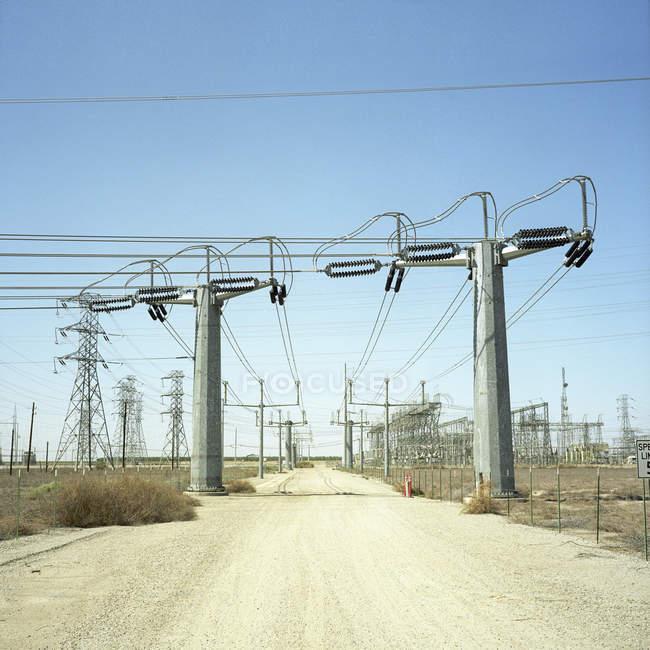 Электрические столбы вдоль пустынной дороги — стоковое фото