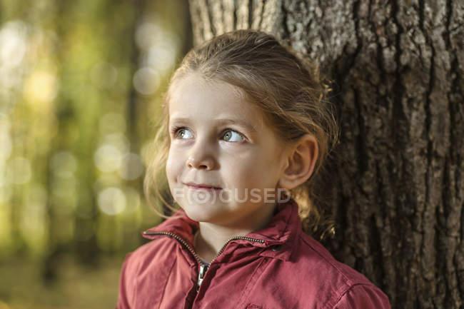 Una ragazza che guarda altrove curiosamente mentre si appoggia ad un tronco d'albero — Foto stock