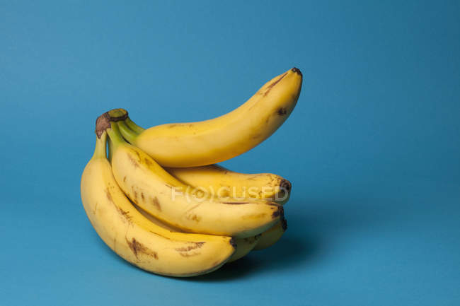 A bunch of bananas with one banana sticking up on blue background — Stock Photo