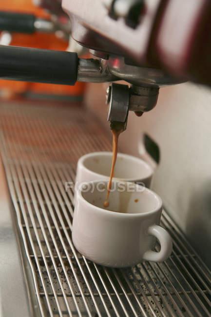 Кава, виливши кави в дві чашки еспресо — стокове фото