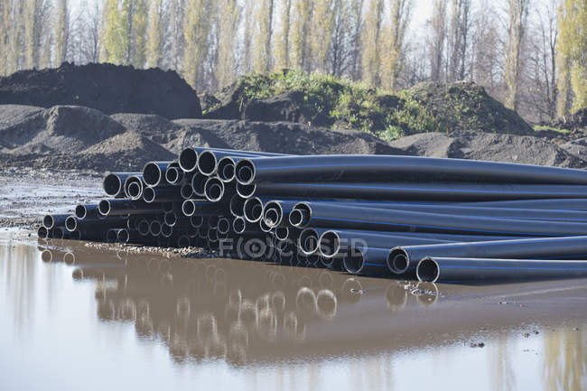 Stack of plastic pipes reflected in water at construction site — Stock Photo