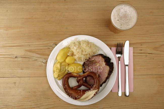 Прямо над подання пластину з кренделі і Німецька традиційної їжі поруч із келих пива — стокове фото