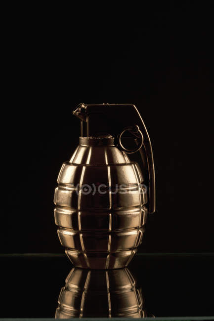 Golden grenade on shiny surface over black background — Stock Photo