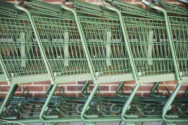 Side view of stacked empty shopping trolleys in row — Stock Photo