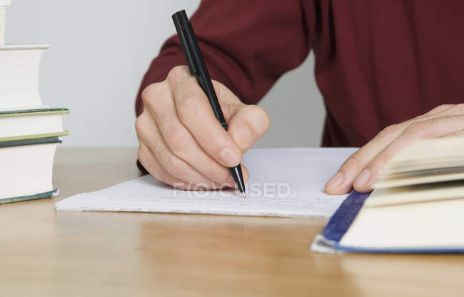 Close-up of man writing in notebook at desk — Stock Photo