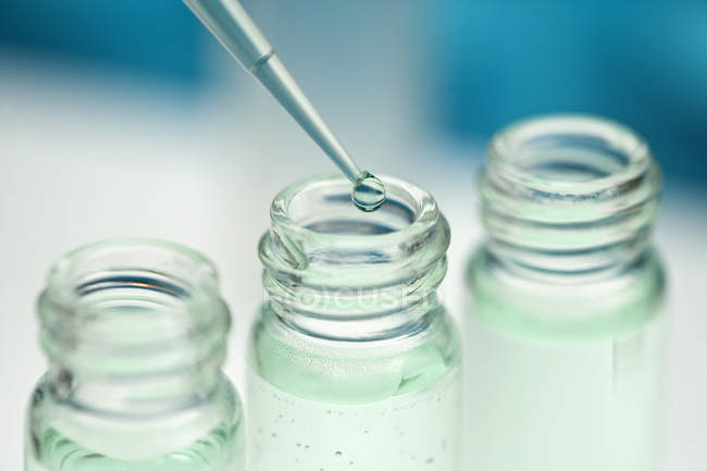 Close up view of pipette dripping in glass jar — Stock Photo