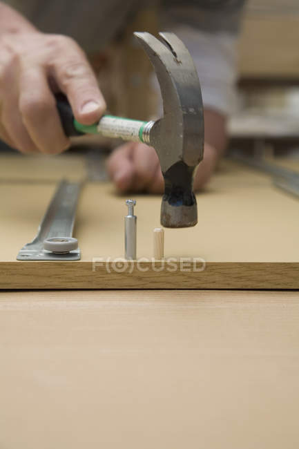 Crop male hand using hammer to assemble furniture — Stock Photo