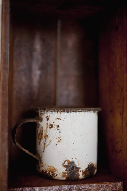 Ржавая металлическая чашка на деревянной полке — стоковое фото
