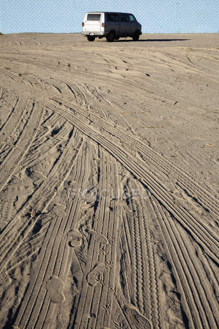 Tyre tracks in sand with vehicle parked at distants — Stock Photo