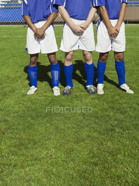 Three soccer players protecting themselves from a free kick — Stock Photo