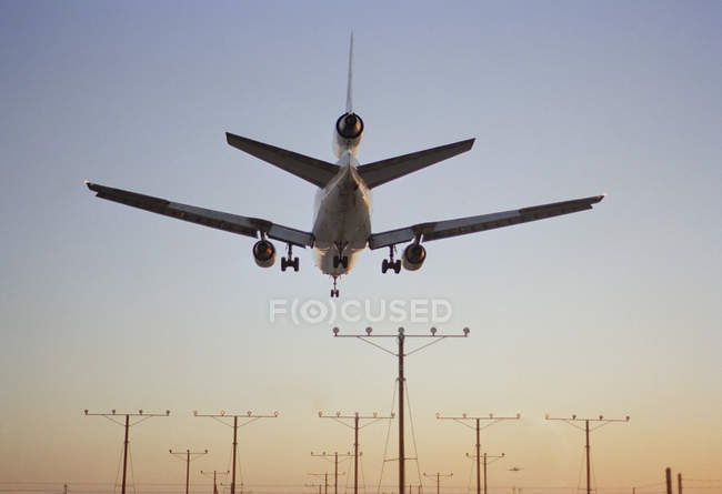 Rear view of airplane landing at dusk — Stock Photo