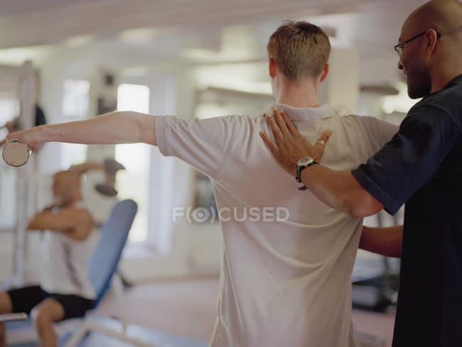 Instructor de ejercicio ayudando al hombre en el gimnasio - foto de stock