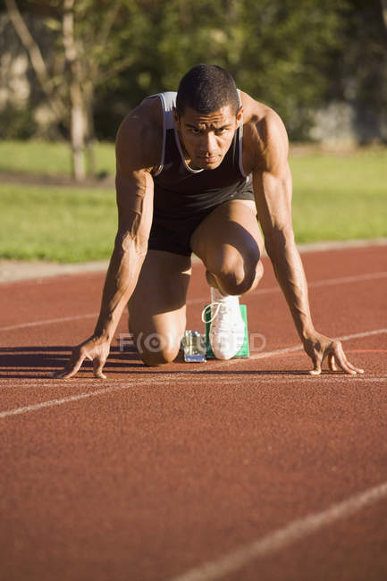 Male athlete in starting blocks on a running track — Stock Photo