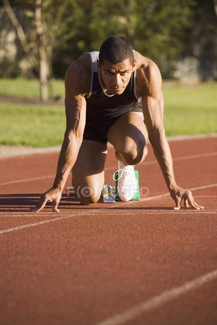 Athlète masculin dans les blocs de départ sur une piste de course — Photo de stock