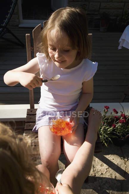 Petite fille assise dans la cour et manger de la gelée — Photo de stock