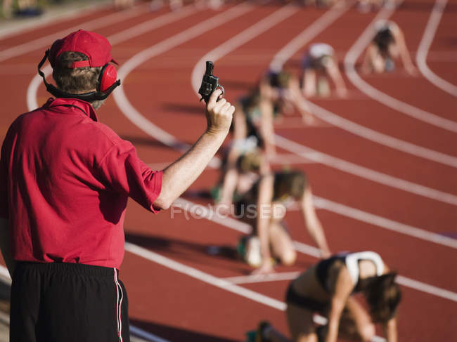 Rear view of race official holding starting gun at beginning of track event — Stock Photo