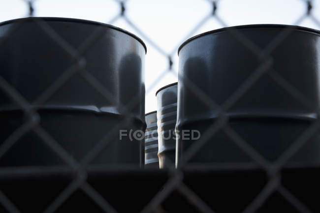 Black barrels seen through wire mesh fence — Stock Photo