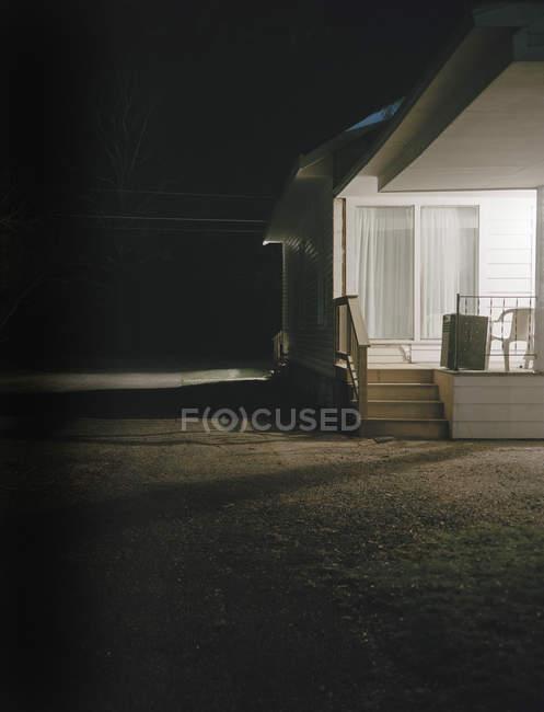 Vista exterior de casa con porche en la noche - foto de stock