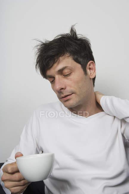 Hombre desaliñado sosteniendo una taza de té - foto de stock