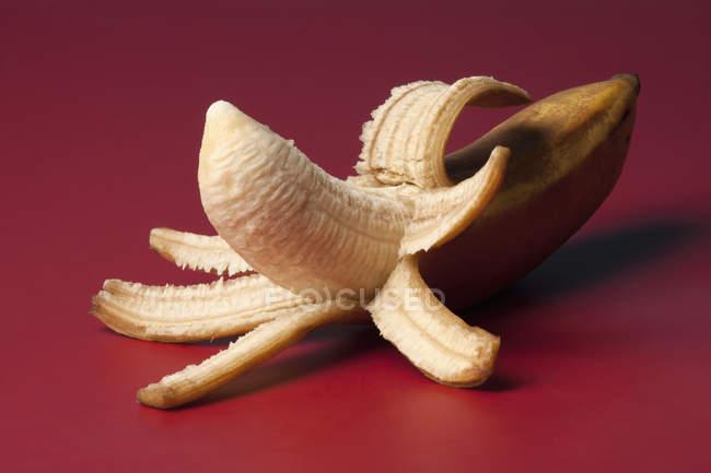 Geschälte Banane auf rotem Grund — Stockfoto