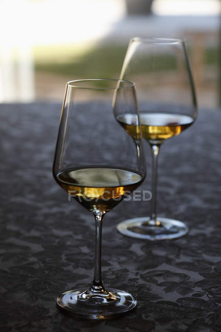 Two glasses of white wine at table — Stock Photo
