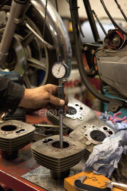 Ernte-Mechaniker-Hand, die Überprüfung mit Zifferblatt Zylinderbohrungen trug Messgerät — Stockfoto