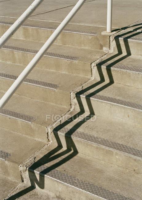 Handrail casting shadow onto concrete steps — Stock Photo