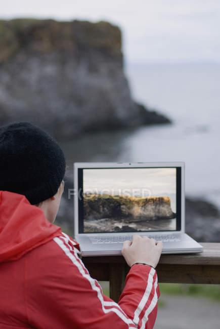 Jovem usando laptop com imagem de paisagem marinha no fundo — Fotografia de Stock