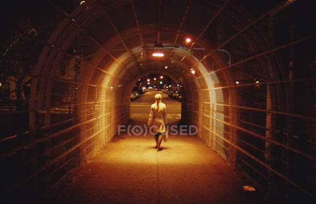 Rear view woman crossing overpass at night — Stock Photo