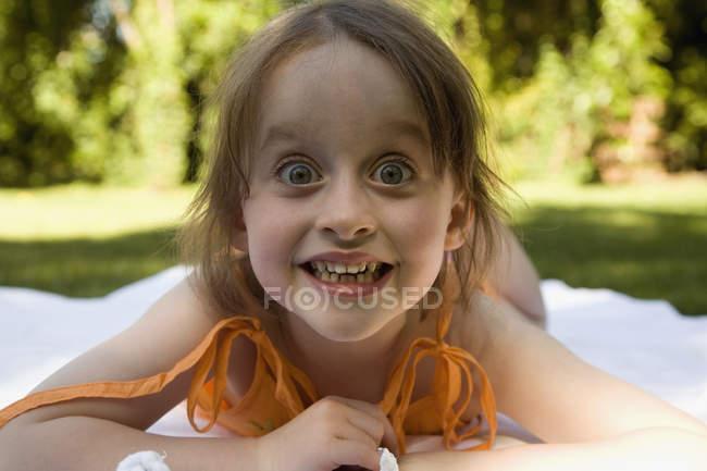 Portrait of little girl lying down on blanket in backyard — Stock Photo