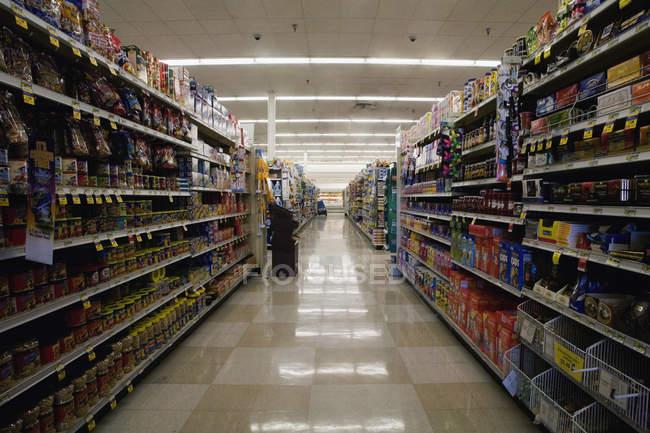 Вид на проход супермаркета между полками магазинов — стоковое фото