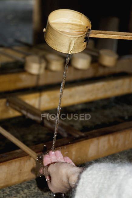 Crop female hands pouring water from wooden ladle — Stock Photo