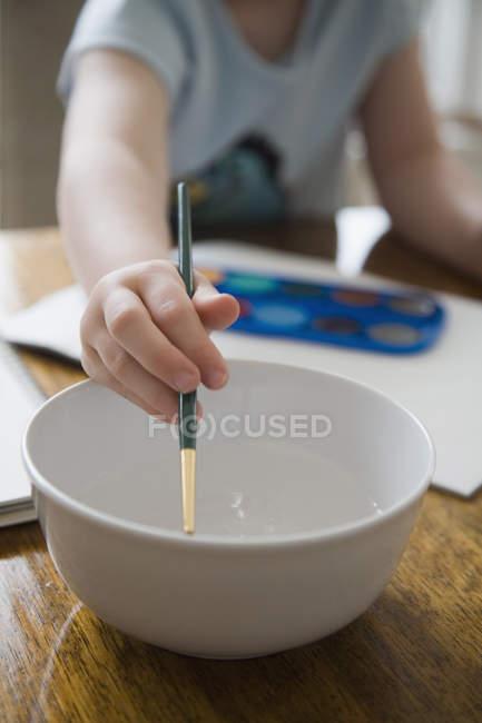 Jovem garota enxaguando pincel em tigela de água — Fotografia de Stock