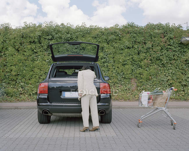 Rear view of woman reaching into car trunk with full shopping cart nearby — Stock Photo