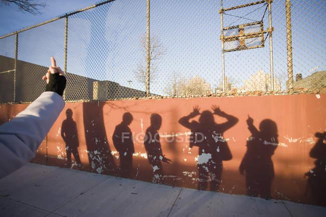 Culture main gesticulant doigt du milieu à des silhouettes de gens sur le mur — Photo de stock