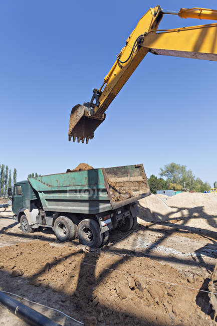 Digger loading soil onto dumper truck — Stock Photo